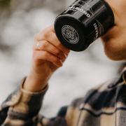 Girl drinking from Inveralmond mug